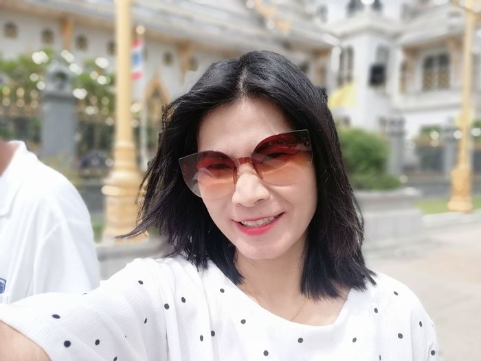 Portrait of woman wearing sunglasses while standing outdoors