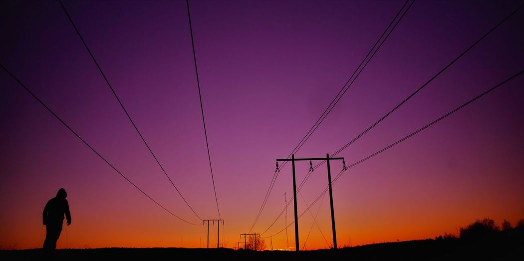 Silhouette of an by electricity pylon against sky during sunset