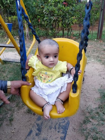 Cropped Hand Of Man By Girl Sitting On Swing