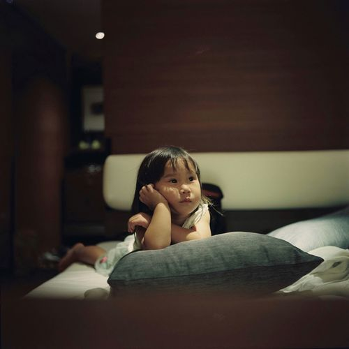 Little girl watching television in bed happily. Little Girl Watching Tv Bed Bedroom Indoors  One Person Real People Lifestyles Home Interior Child Sitting Girls Leisure Activity Looking At Camera Furniture Portrait Women Sofa Childhood Front View Casual Clothing Relaxation Teenager Contemplation