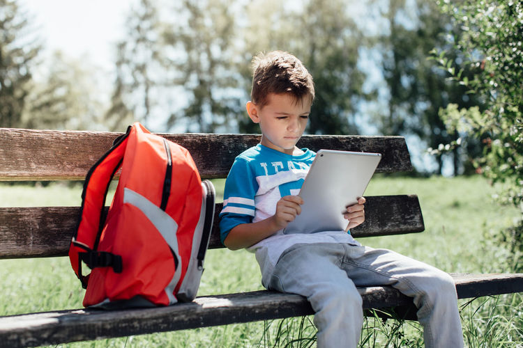 A schoolboy on a bench taking a break and playing on a tablet 6 Alone Bag Bench Boy Browse Caucasian Child Childhood Children And Technology Concentration Education Green Horizontal Information Kid Lifestyle Natural Light One Person Out Of School Outdoors Park Schoolboy Tablet Technology