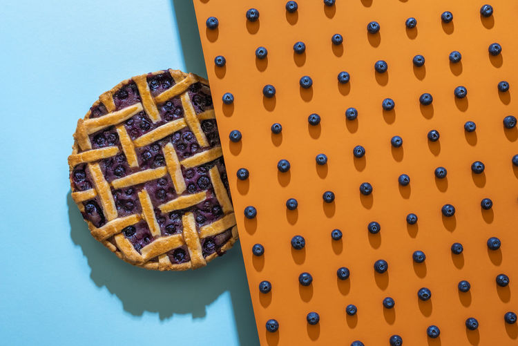 High angle view of blueberry pie on blue background