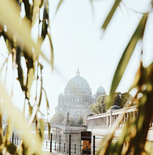 Berlin cathedral by spree river against sky seen through leaves