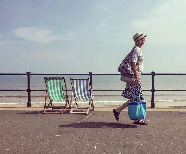 Side view of woman walking with bags on promenade by sea against sky