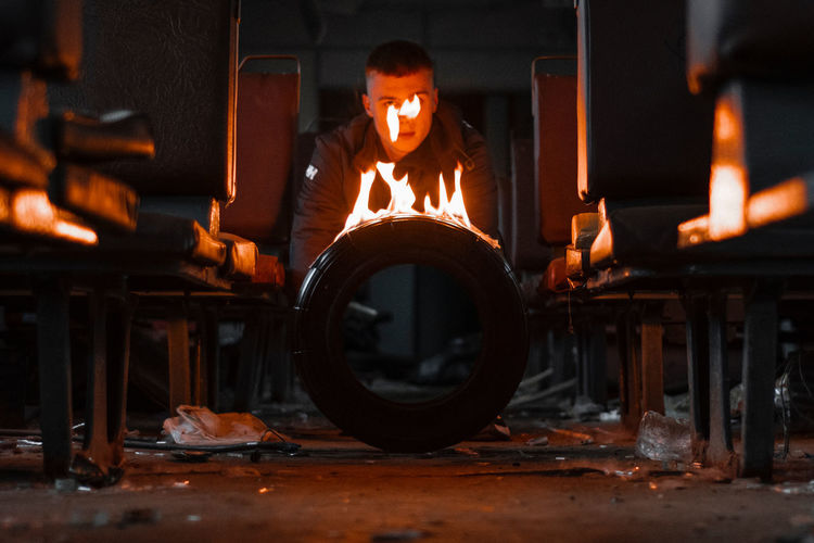 Close-up of burning tire against man in background in train