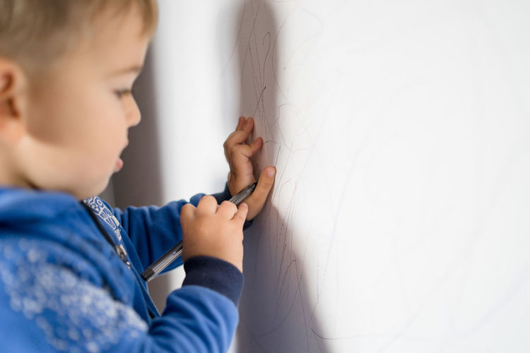 Side View Of Boy Drawing On Wall