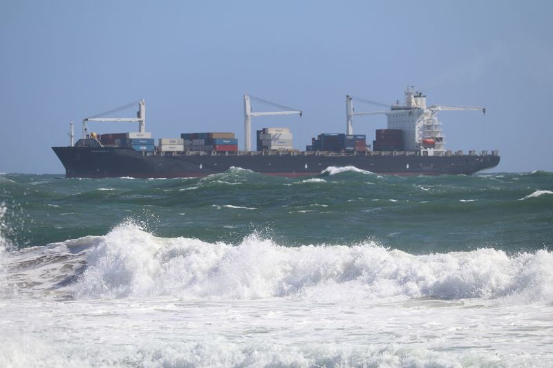 Container ship sailing in sea against clear sky