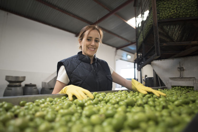 Portrait of smiling woman standing by olives in warehouse