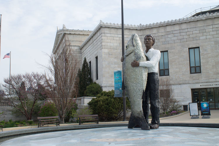 Large Sculpture Of Man Holding Fish Against Shedd Aquarium