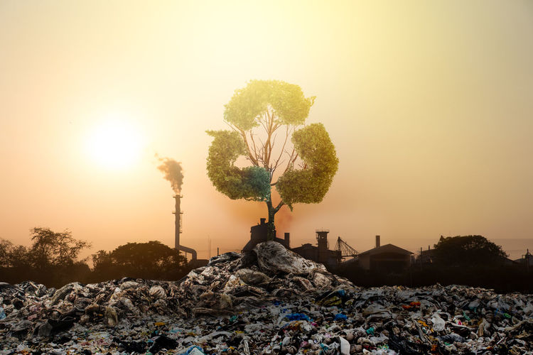 Digital composite image of recycling symbol over garbage and factory against orange sky