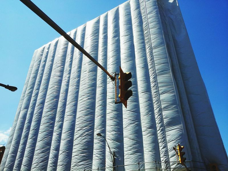 Canada, Ontario. Windsor, 2016. Exterior wall restoration of a downtown federal building enters the wrap the scaffolding stage making it look a like a large art installation. Architecture Restoration Art? Plastic Wrap