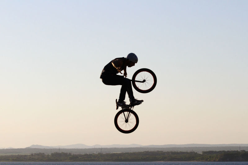 Man with bicycle jumping over sea against clear sky