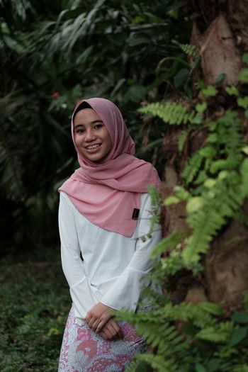 Portrait of smiling teenage girl wearing hijab standing by plants at park
