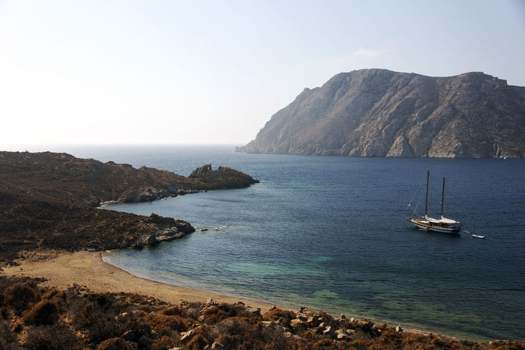 Aerial view of a coast of island of patmos, Greece Beach Beauty In Nature Clear Sky Day Land Mode Of Transportation Mountain Nature Nautical Vessel No People Non-urban Scene Outdoors Rock Sailboat Scenics - Nature Sea Sky Tranquil Scene Tranquility Transportation Water Yacht