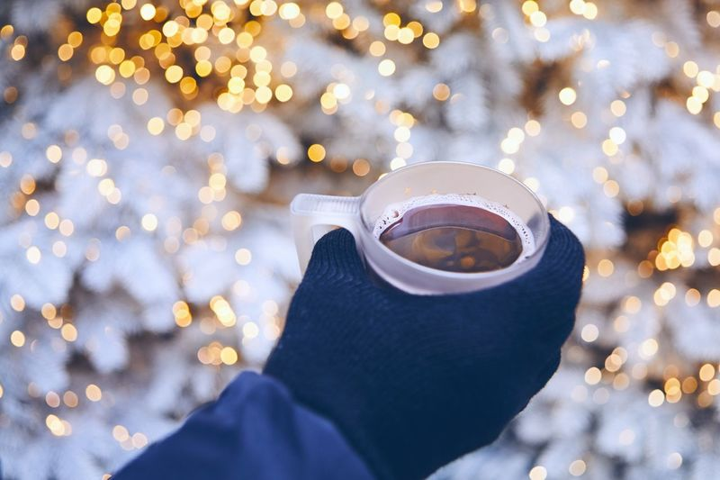 Cropped Hand Of Person Holding Coffee Cup Against Illuminated Lights During Winter