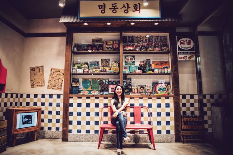 Vintage Korea. Lotte World Tower is one of the tallest buildings in the world located in Jamsil area in Seoul in South Korea. It boasts massive food court, one of which is Vintage Korea themed, decorated with old movie posters and products of olden times Hidden Gems  South Korea Vintage Korea Seoul Asian Girl Portrait Exhibition Brightly Lit Nikon D750 Casual Clothing Looking At Camera Full Body Shot People And Places TakeoverContrast