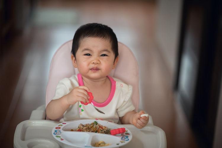 Cute baby girl eating food at home
