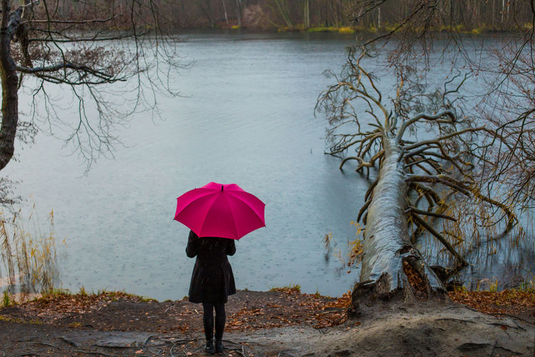 A woman stands alone in cloudy rainy weather by a lake Water Umbrella Protection Security Nature Rain Day Tree One Person Lake Outdoors Weather Weather Report Cloudy Umcomfortable Lonely Rainy Sad Autumn Rain Woman Red Depression Sadness Loneliness