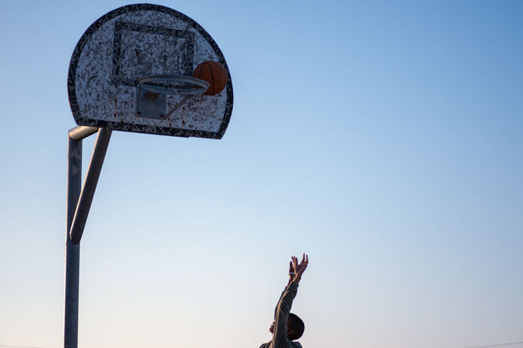Low angle view of boy throwing ball in basketball hoop against clear sky
