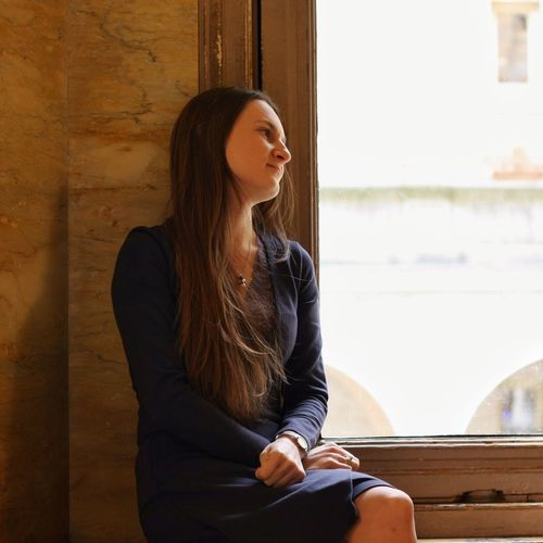 Thoughtful woman sitting by window at home