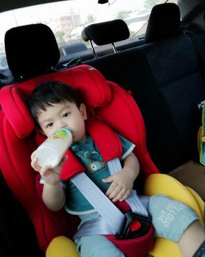 Cute boy sitting in toy car