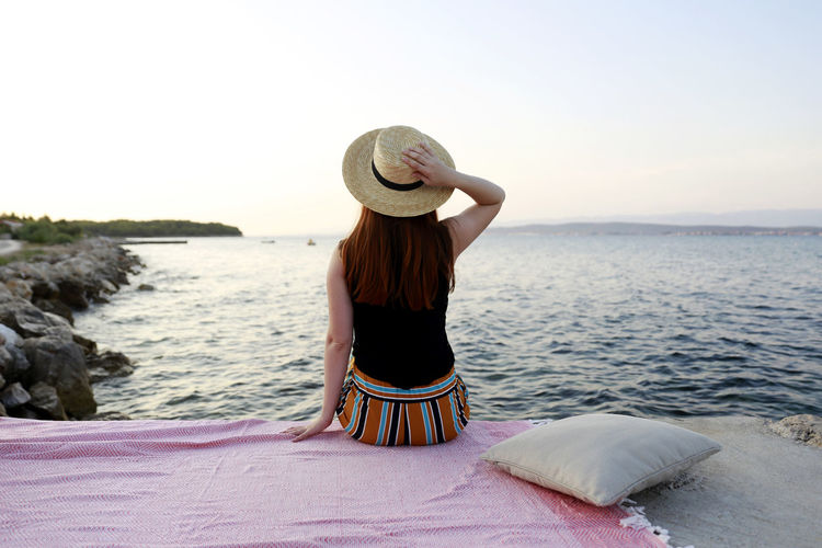 Rear view of woman wearing hat looking at sea