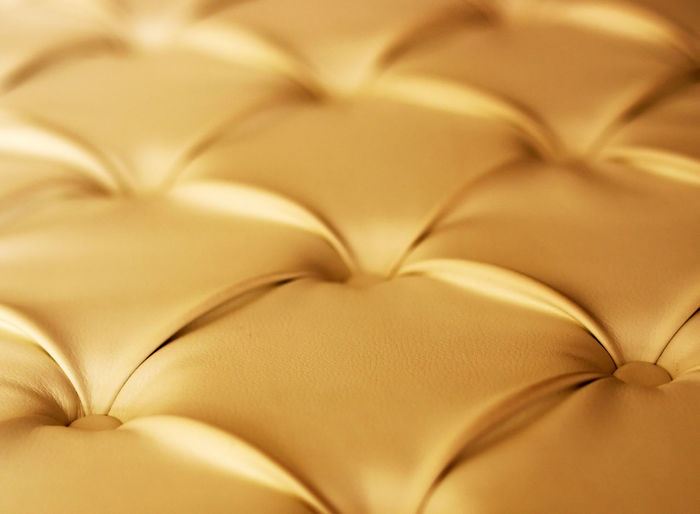Close-Up Of Gold Chesterfield Sofa
