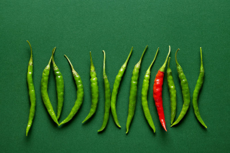 Green chilli peppers lined up with a single red hot chilli pepper on a green background. Top view Green Color Vegetable Studio Shot Food Colored Background Indoors  Healthy Eating Freshness Wellbeing Green Background No People Still Life Directly Above Group Of Objects Chili Pepper Pepper Close-up Bean Red Black Background Contrast Copy Space