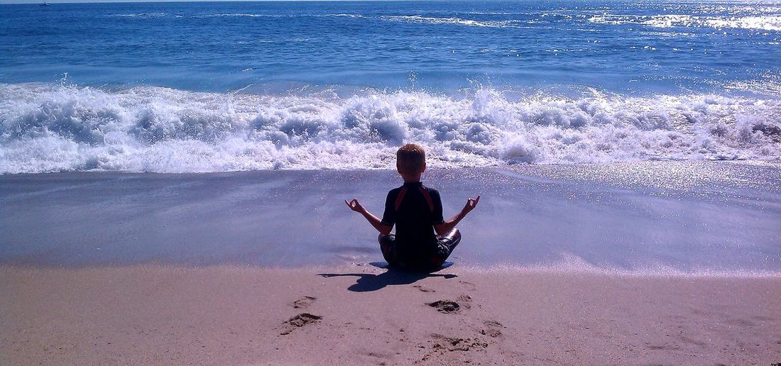 Rear view of boy meditating on shore at beach