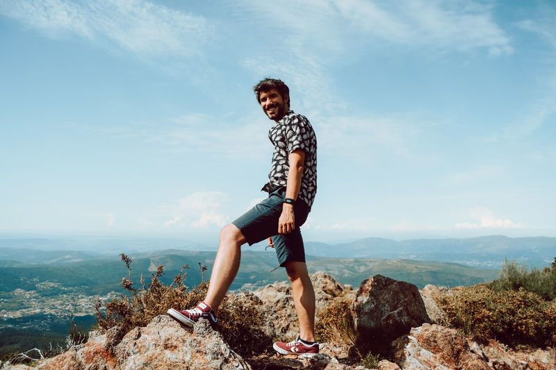 Young man standing on rock against sky