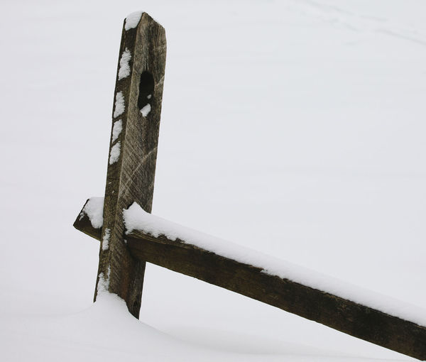 Low angle view of snow covered metal against sky