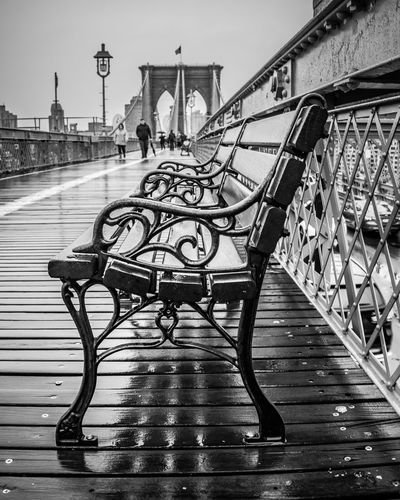 Wrought Iron bench on the Brooklyn Bridge on a rainy day Brooklyn Bridge  New York Reflection Architecture B&w Beauty In Nature Bench Black And White Blancoynegro Bridge Built Structure Connection Rainy Seat Suspension Bridge Travel Destinations Walking Wrought Iron
