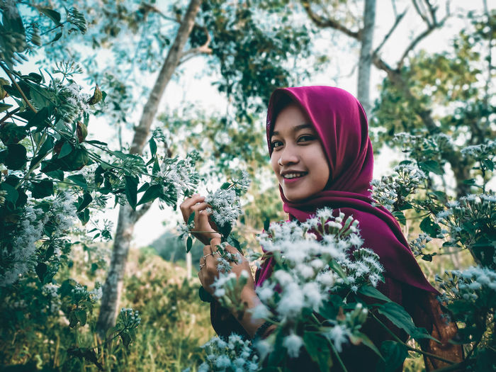 Portrait of smiling young woman against plants and trees