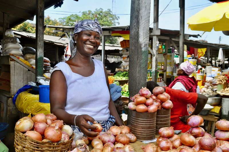 Portrait of a smiling woman selling onions at makola market in accra, ghana
