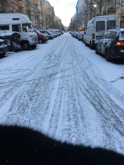 Snow covered road in city