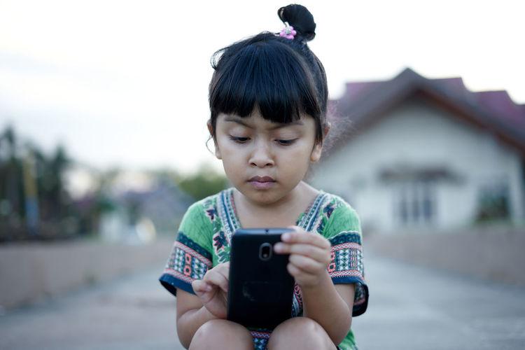 Girl using phone while sitting on land