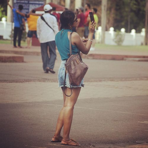 Rear view of woman photographing on city street