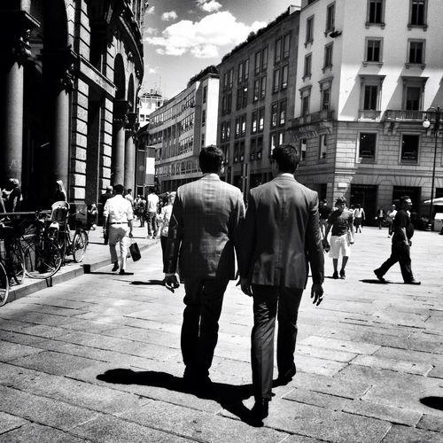 Rear view of businessmen walking on street in city