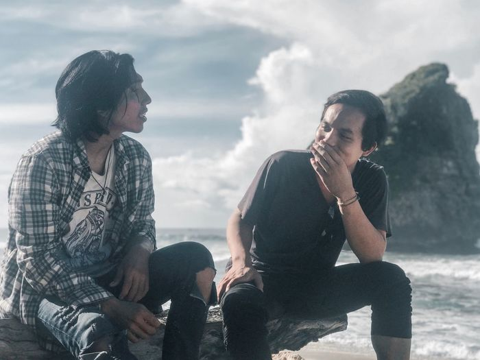 Young men sitting on rock at beach against sky