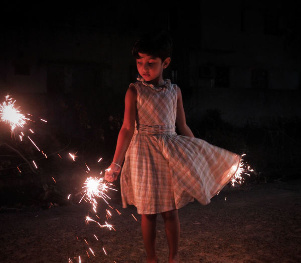 Girl holding sparklers while standing at night
