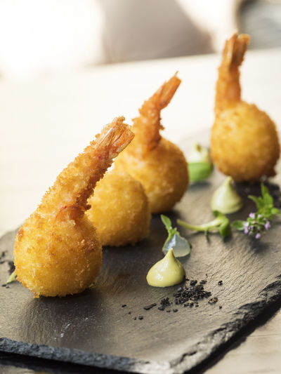 Close-up of shrimps and mozzarella corn on cutting board over table