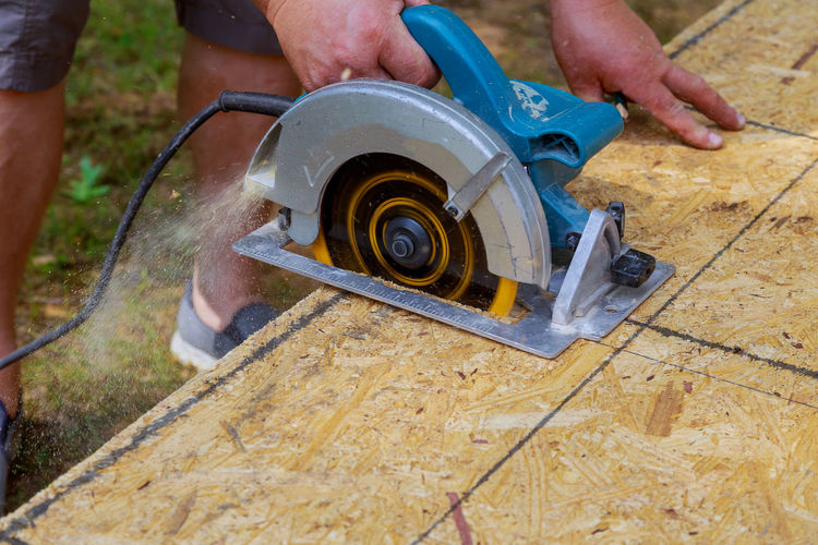 Low section of man using circular saw on wood