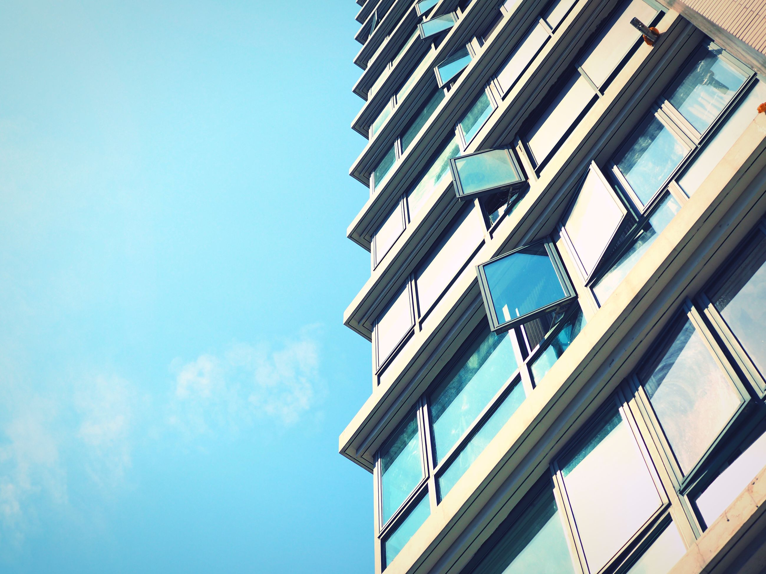 architecture, low angle view, built structure, building exterior, building, clear sky, window, city, blue, sky, residential building, tower, day, residential structure, tall - high, office building, directly below, outdoors, modern, balcony