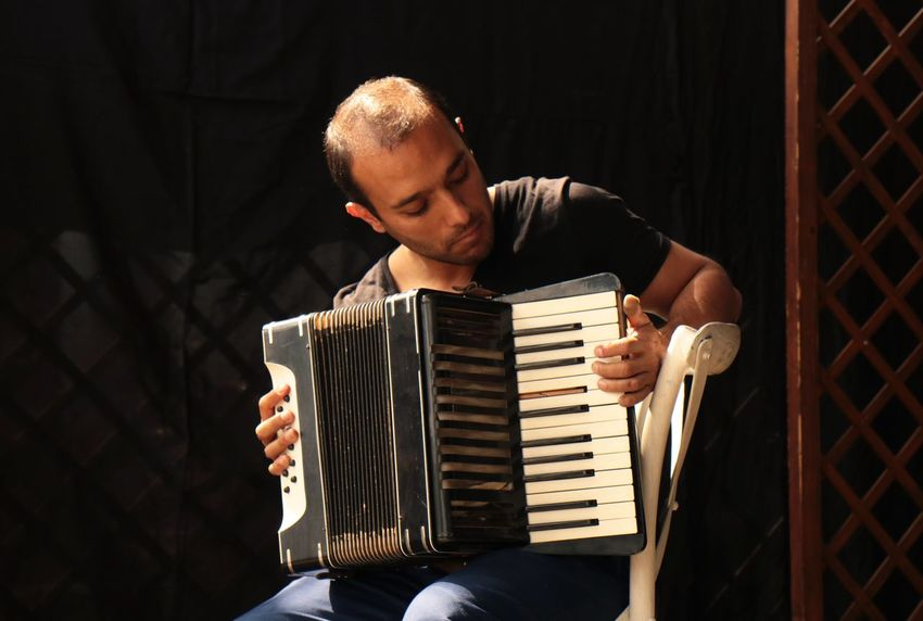 Musician Music One Person Arts Culture And Entertainment Musical Instrument Accordion Playing Real People Front View Indoors  Musician Young Adult Skill  Performance Musical Equipment Artist Sitting Young Men Casual Clothing Leisure Activity Stage