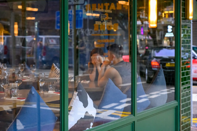 Couple seen through glass window of restaurant