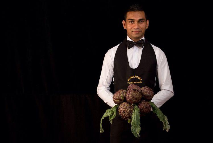 Portrait Of Male Waiter Holding Vegetable Against Black Background