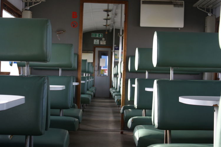 An empty train that's retro style and used for a museum eating area. Absence Chair Day Diminishing Perspective Empty Furniture Hipster Illuminated In A Row Modern No People Repetition Seat The Way Forward