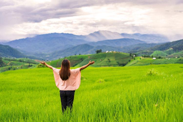 Rear view of woman walking on field