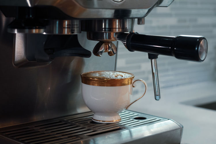Close-up of coffee cup and espresso machine