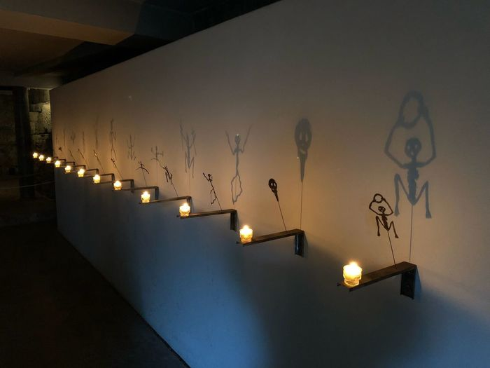 Illuminated lighting equipment on wall at night